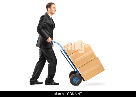 Full length portrait of a businessman pushing a hand truck full with cardboard boxes - Stock Photo