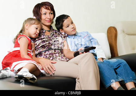 a young mother with two kids, a boy and a girl, is sitting on a sofa and watching a tv - Stock Photo