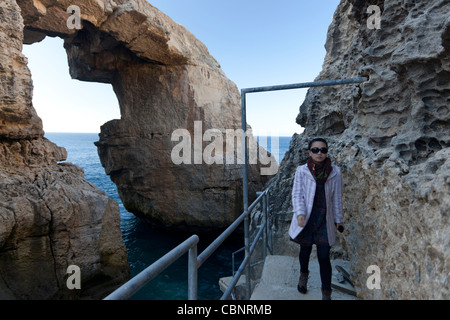 A natural and dramatic rocky arch at the point where Mielah Valley reaches the sea in Gharb in west Gozo. - Stock Photo