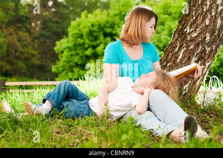 young mother sitting in grass under tree and reading book to her small daughter who is lying on knees of her mother and sleeping