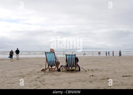 Deck Chairs At British Seaside In Summer With Elderly