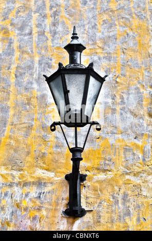 old lantern on yellow wall in street of Tallin old town, Estonia - Stock Photo