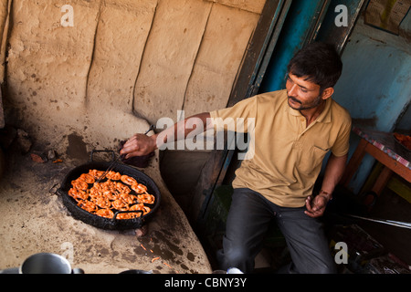 India, Manipur, Lairouching Hills, food, man cooking jelabi in small roadside cafe - Stock Photo