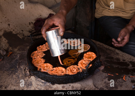 India, Manipur, Lairouching Hills, food, hands of man cooking jelabi in small roadside cafe - Stock Photo