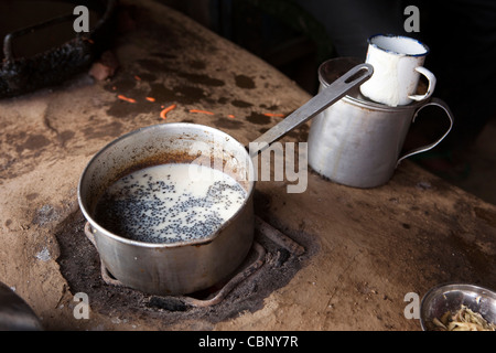 India, Manipur, Lairouching Hills, food, small roadside café, chai (tea) being cooked in saucepan on primitive stove - Stock Photo