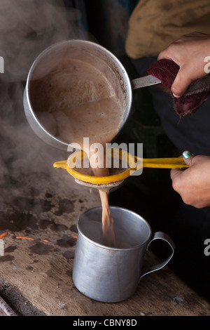India, Manipur, Lairouching Hills, food, small roadside café, chai (tea) being strained into cup - Stock Photo
