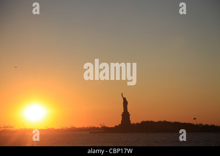 Sunset with Statue of Liberty - Stock Photo