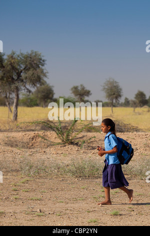 Young Indian girl in school uniform walking barefoot to her school near Rohet in Rajasthan, Northern India - Stock Photo