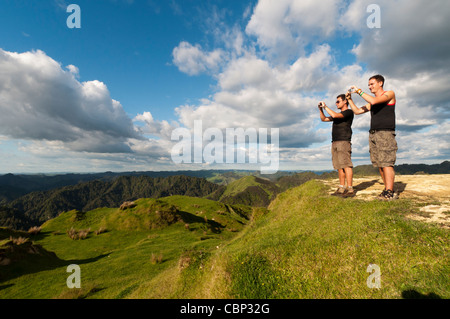 Two young backpackers taking picture with cameras, Blue duck lodge, Whakahoro, Ruapehu District, New Zealand - Stock Photo