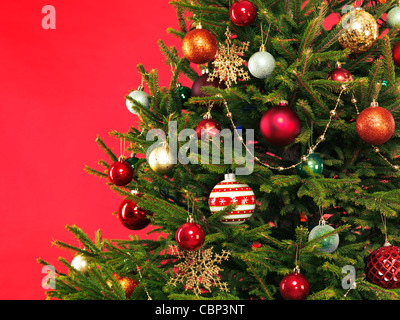 Closeup of Christmas tree colorful decoration on bright red background - Stock Photo