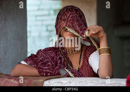 Pretty young Indian woman covering her face at home in Narlai village in Rajasthan, Northern India - Stock Photo