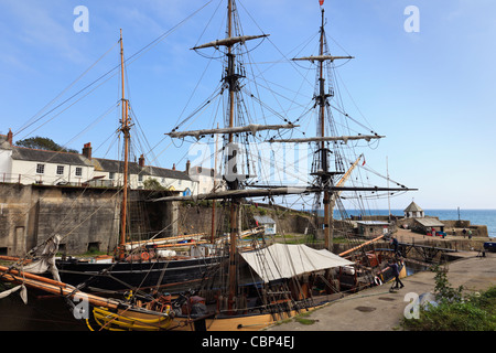 Pheonix and other Tall Ships in the inner harbour with old cottages on the quayside. Charlestown, Cornwall, England, - Stock Photo