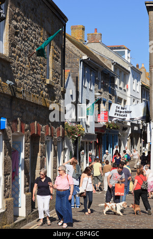 Shops on a narrow cobbled street busy with tourists in St Ives, Cornwall, England, UK, Britain. - Stock Photo