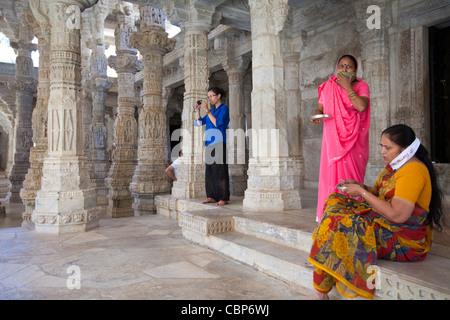 Jain pilgrims with traditional masks at The Ranakpur Jain Temple at Desuri Tehsil in Pali District, Rajasthan, India - Stock Photo