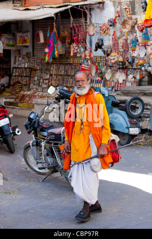 Hindu sadhu holy man wearing traditional robes walks in old town in Udaipur, Rajasthan, Western India - Stock Photo