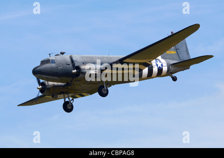 Douglas C-47A Skytrain, military version of the DC-3 Dakota,in USAAF D-Day markings on approach for landing At RAF - Stock Photo