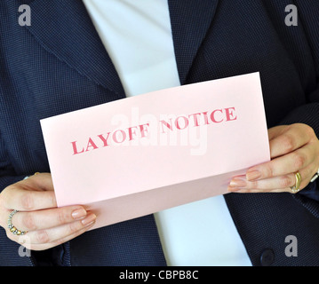 Female executive reading a layoff notice from her employer - Stock Photo