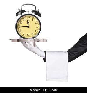 A hand holding a silver tray with a retro clock alarm on it - Stock Photo