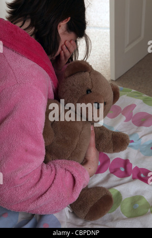 Over the shoulder irl clutching a teddy bear sitting on her bed hand over her eyes crying. - Stock Photo