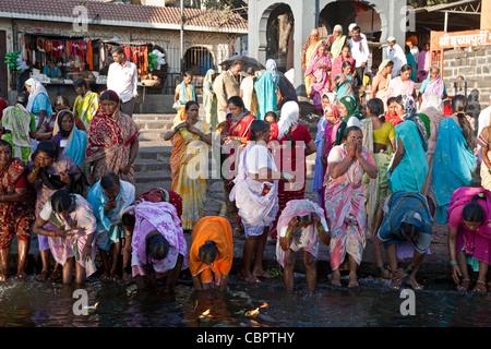 Women taking the ritual bath in the sacred waters of the Godavari river. Ram Kund. Nasik. India - Stock Photo