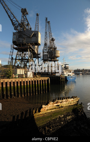 Old dockyard cranes on a harbour side jetty with an old rotting hulk in the foreground. Cloudy blue sky with moody - Stock Photo