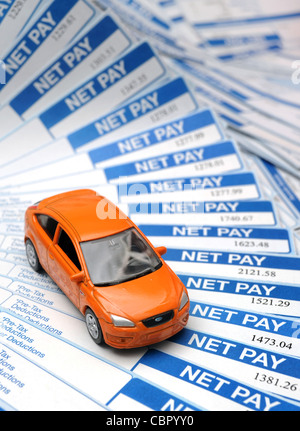BRITISH PAYSLIPS WITH MODEL CAR RE INCOMES WAGES JOBS RISING INFLATION BILLS HOUSEHOLD BUDGETS SALARIES NET PAY - Stock Photo