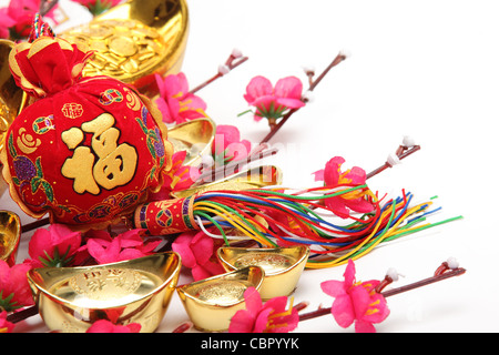 Chinese New Year Decorations,Closeup on money bag with gold ingots and plum blossom. - Stock Photo
