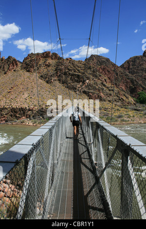 a woman hikes across silver bridge over the Colorado River at the bottom of the Grand Canyon, Arizona - Stock Photo
