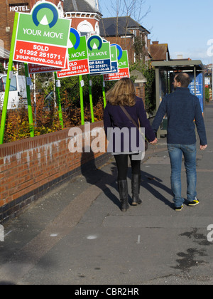 Young couple walking down road looking at House for sale and house sold signs on a street in central Exeter UK - Stock Photo