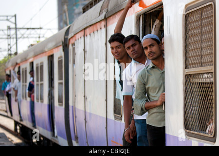 Workers on crowded commuter train of Western Railway near Mahalaxmi Station on the Mumbai Suburban Railway, India - Stock Photo