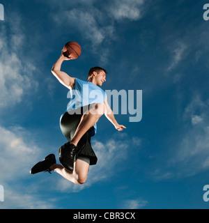 Caucasian man playing basketball - Stock Photo