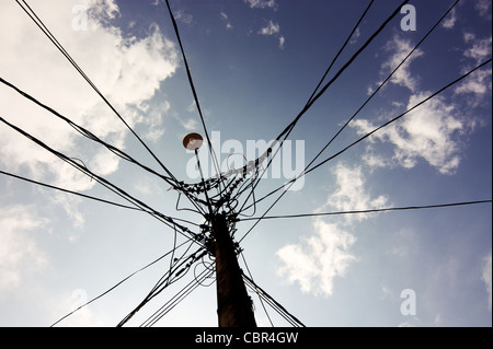 Silhouette of a lamp post photographed against a blue sky and white clouds. Multiple wires are attached to this - Stock Photo