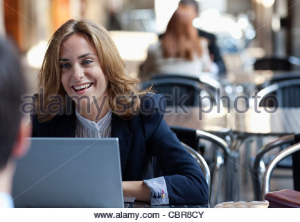 Business people working together in sidewalk cafe - Stock Photo