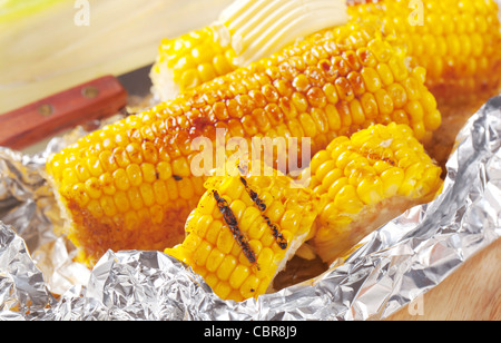 Pieces of sweet corn grilled in tin foil - Stock Photo