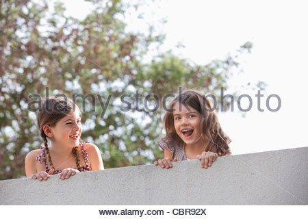Girl watching friend screaming over wall - Stock Photo