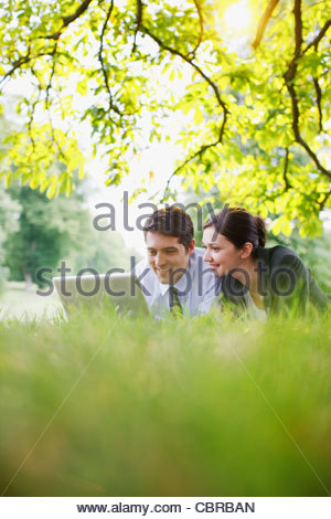 Business people using laptop on ground in park - Stock Photo