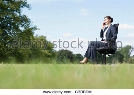 Businesswoman sitting in chair talking on cell phone outdoors - Stock Photo