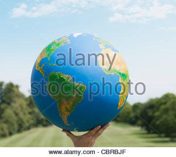Hand holding large globe outdoors - Stock Photo