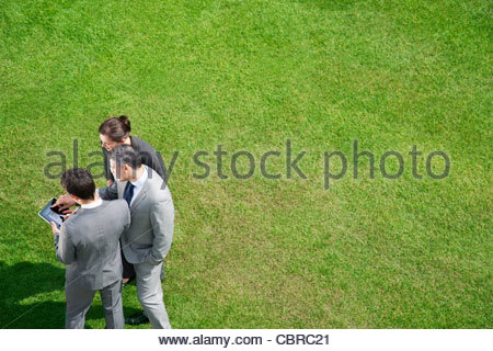 Business people using digital tablet together outdoors - Stock Photo