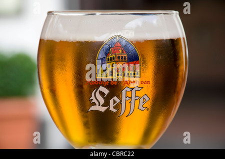 Horizontal close up of a Leffe blond beer in a traditional goblet shaped glass. - Stock Photo