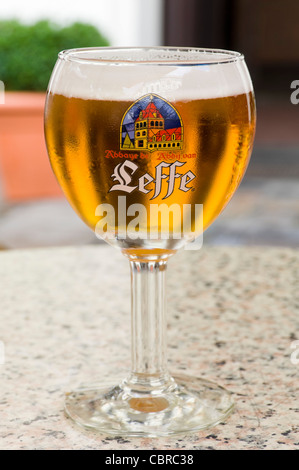 Vertical close up of a Leffe blond beer in a traditional goblet shaped glass. - Stock Photo