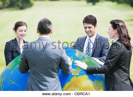 Business people standing outdoors with large ball - Stock Photo