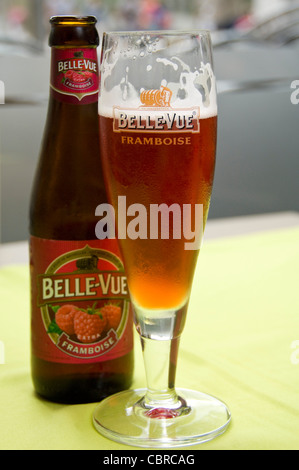 Vertical close up of a traditional Fruit Lambic Belgian beer bottle and distinctive flute shaped glass. - Stock Photo