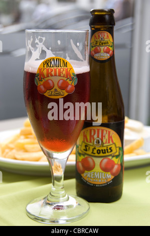 Vertical close up of a traditional Fruit Lambic Belgian beer bottle and glass infront of a plate of chips and mayo. - Stock Photo