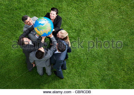 Business people lifting globe together outdoors - Stock Photo