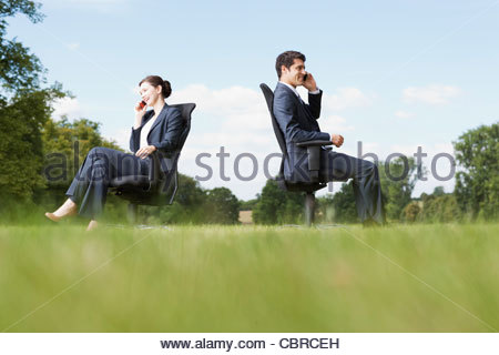 Business people sitting in chairs outdoors talking on cell phones - Stock Photo