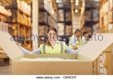 Smiling young woman opening a carton box, relocation and ...
