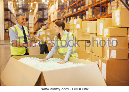Workers checking box in warehouse - Stock Photo