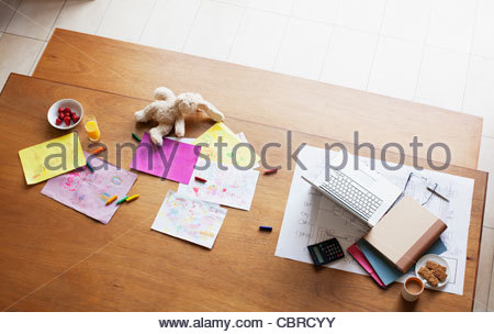 Table covered with papers and laptop - Stock Photo