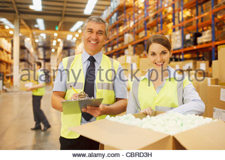 Workers in warehouse standing near box - Stock Photo